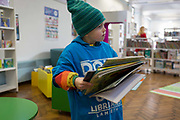 A young reader collects books to borrow in the re-opened Carnegie Library on Herne Hill in south London which has opened its doors for the first time in almost 2 years, on 15th February 2018, in London, England. Closed by Lambeth council and occupied by protesters for 10 days in 2016, the library bequeathed by US philanthropist Andrew Carnegie has been locked ever since because, say Lambeth austerity cuts are necessary. A gym that locals say they dont want or need has been installed in the listed basement and actual library space a fraction as before and its believed no qualified librarians will be present to administer it. Protesters also believe this community building will ultimately sold off by Lambeth council for luxury homes.