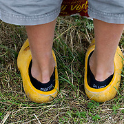 Nederland Giessen  26 augustus 2009 200900826 ..Serie levensmiddelensector. Close up klompen jongen, tegenstelling moderne lage puma sokken en ouderwetse klompen. Closeup, contradiction modern sport socks and old fashioned wooden shoes. ..Foto: David Rozing