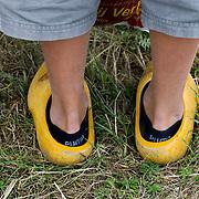 Nederland Giessen  26 augustus 2009 200900826 ..Serie levensmiddelensector. Close up klompen jongen, tegenstelling moderne lage puma sokken en ouderwetse klompen. Closeup, contradiction modern sport socks and old fashioned wooden shoes. ..Foto: David Rozing