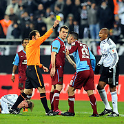 Referee's Cuneyt CAKIR (L) show the yellow card to Trabzonspor's Sezer BADUR (2ndR) during their Turkey Cup Group B matchday 5 soccer match Besiktas between Trabzonspor at the Inonu stadium in Istanbul Turkey on Wednesday 26 January 2011. Photo by TURKPIX