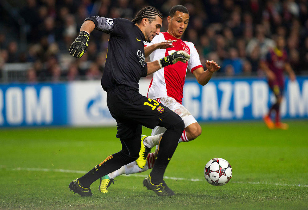 Barcelona goalkeeper Jose Manuel Pinto in duel for the ball with Ajax's Ricardo Van Rhijn during the Group H Champions League soccer match between Ajax and FC Barcelona at the ArenA stadium in Amsterdam, Netherlands, Tuesday Nov. 26, 2013. (AP Photo/Patrick Post)