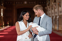 """File photo dated 08/05/19 of the Duke and Duchess of Sussex with their baby son Archie Harrison Mountbatten-Windsor, during a photocall in St George's Hall at Windsor Castle in Berkshire. The royal couple have announced they are to """"step back"""" as senior members of the royal family and will now divide their time between the UK and North America."""