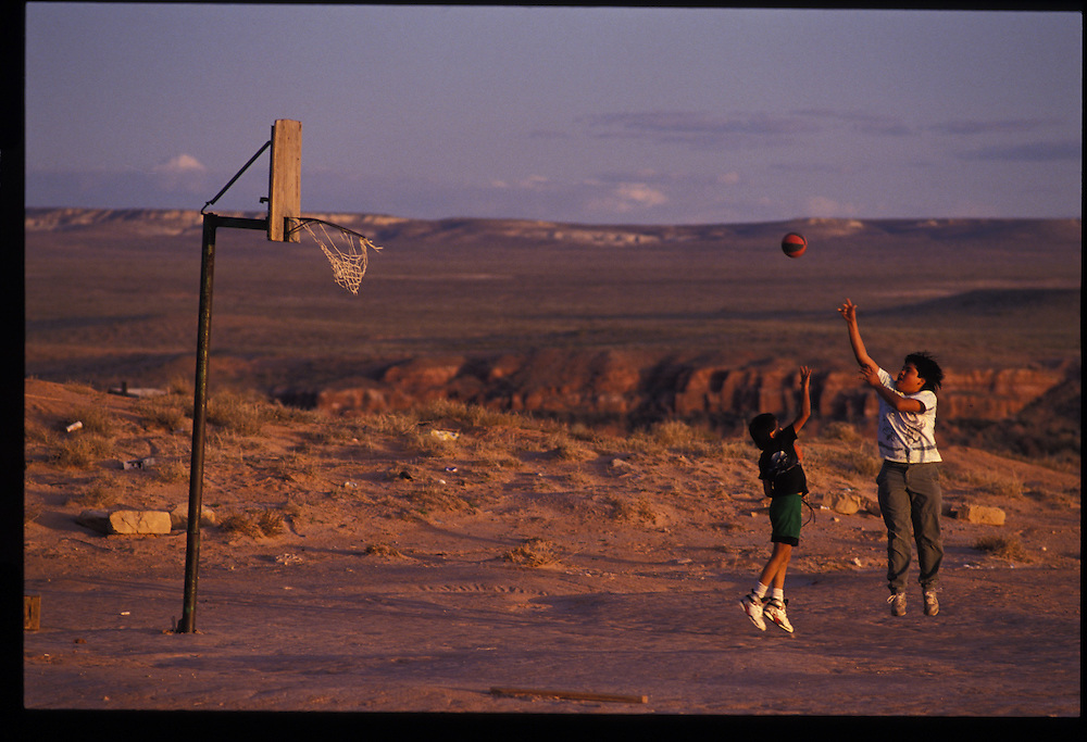 Junior Billy(10) and Fabian Denesto(15) play basketball at the site of the old airport in Tuba City.  Thousands of kids in isolated sheep camps learn to shoot through homemade bailing-wire hoops.  1993