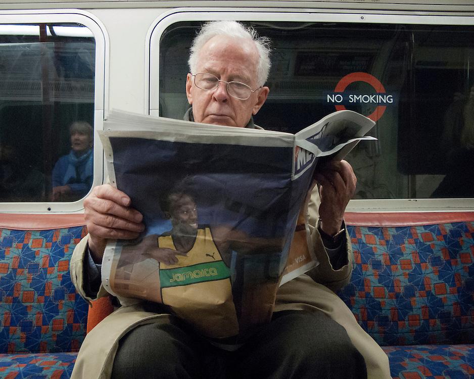 Man Reading a newspaper on the London Underground