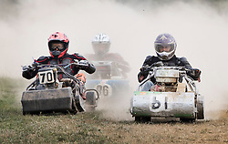 © Licensed to London News Pictures. 24/09/2016. Five Oaks, UK. Competitors ride through the dust as they take part in a race at the Lawn Mower Racing World Championships. A weekend long set of races using specially adapted lawn mowers will see a World Champion announced on Sunday. Photo credit: Peter Macdiarmid/LNP