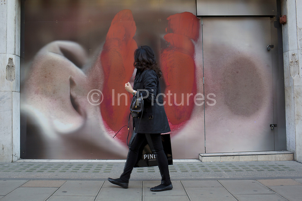 Hoarding outside a shop under refurbishment makes an interesting street scene on New Bond Street, London, UK. A weird visual juxtaposition is created as people integrate with the large scale printed photograph. A big pair of red lipstick covered lips looks like it is eating a passing woman.