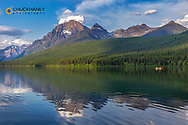 Fishing from a red canoe on the calm waters of Bowman Lake in Glacier National Park, Montana, USA