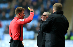 Referee Anthony Backhouse shows Peterborough United's Manager Steve Evans a yellow card during the match