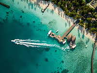 Aerial view of traditional boat with passengers sailing next to Maldives island.