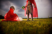 Two boys in red capes play at sunset, one is shooting the other with a toy bubble gun.