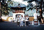 group posing with traditional stick by the statue of the 1000 hand Buddha, Shikoku Japan 1980s