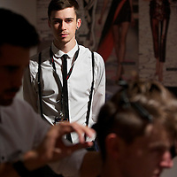 A barber trims hair while another looks on in the lobby of the BFC show space at Somerset House, London on 22  September 2010.