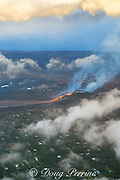 Aerial view of Kilauea Volcano east rift zone erupting hot lava from Fissure 8 in the Leilani Estates subdivision near the town of Pahoa. The lava pours out of the cinder cone and drains downhill as an incandescent river through Puna District, Hawaii Island ( the Big Island ), Hawaiian Islands, U.S.A.