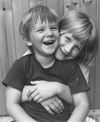 Young girl with arms around younger brother both smiling,