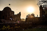 """29th January 2015, New Delhi, India. View of the ruins of Feroz Shah Kotla as believers move through them praying, making offerings and asking for their wishes to be granted by Djinns in the ruins of Feroz Shah Kotla in New Delhi, India on the 29th January 2015<br /> <br /> PHOTOGRAPH BY AND COPYRIGHT OF SIMON DE TREY-WHITE a photographer in delhi. + 91 98103 99809. Email:simon@simondetreywhite.com<br /> <br /> People have been coming to Firoz Shah Kotla to leave written notes and offerings for Djinns in the hopes of getting wishes granted since the late 1970's. Jinn, jann or djinn are supernatural creatures in Islamic mythology as well as pre-Islamic Arabian mythology. They are mentioned frequently in the Quran  and other Islamic texts and inhabit an unseen world called Djinnestan. In Islamic theology jinn are said to be creatures with free will, made from smokeless fire by Allah as humans were made of clay, among other things. According to the Quran, jinn have free will, and Iblīs abused this freedom in front of Allah by refusing to bow to Adam when Allah ordered angels and jinn to do so. For disobeying Allah, Iblīs was expelled from Paradise and called """"Shayṭān"""" (Satan).They are usually invisible to humans, but humans do appear clearly to jinn, as they can possess them. Like humans, jinn will also be judged on the Day of Judgment and will be sent to Paradise or Hell according to their deeds. Feroz Shah Tughlaq (r. 1351–88), the Sultan of Delhi, established the fortified city of Ferozabad in 1354, as the new capital of the Delhi Sultanate, and included in it the site of the present Feroz Shah Kotla. Kotla literally means fortress or citadel."""