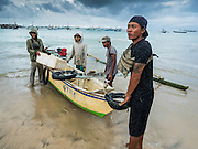 18 JULY 2016 - KUTA, BALI, INDONESIA:  A fisherman brings his small outrigger canoe into shore at Pasar Ikan pantai Kedonganan, a fishing pier and market in Kuta, Bali.   PHOTO BY JACK KURTZ