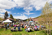 A crowd sits outside on picnic tables for a concert at the Gold Hill Inn in Gold Hill, Colorado.