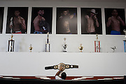 A staff member mounts a UFC championship belt to the wall above the octagon at Jackson Wink MMA in Albuquerque, New Mexico on June 9, 2016.