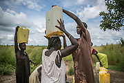 Elizabeth Ngobi, 35, right, helps Nyatut Jok, center, carry a water bucket as Rebecca Agani, far left, awaits after fetching the water from the pump inside Bidibidi refugee settlement in Uganda. Elizabeth was raped by six Dinka soldiers in July 2015 in Juba and was shortly transferred to the UN compound. She had four children with her husband, but gave birth to a girl from the rape in early 2016 after she came to Uganda's Pagirinya refugee settlement. Her husband ran away from the fighting and she hasn't heard about him or her parents ever since.