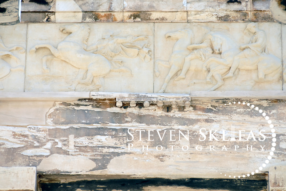 Acropolis. Athens. Greece. Close up view of part of the inner chamber Ionic frieze of the Parthenon Temple in Athens. The Frieze represented the Panathenaic procession surrounded the entire inner chamber of the temple and consisted of 115 one metre high marble blocks featuring over 350 human figures and divinities and at least 200 animals, mostly horses. The Frieze was created under the direction of the famous Greek sculptor Phidias or Pheidias. The Parthenon, a temple dedicated to the goddess Athena (Athena Parthenos), was constructed and decorated between 447 and 432 BC. The Parthenon is a Doric style peristyle temple with 17 fluted columns along each side and eight at the ends, which lean slightly inward and bulge out in the centre to cunningly offset the natural optical distortion. The entire Temple, apart from the roof,  were of white Pentelic marble with the sculptures that once decorated the pediments, friezes and metopes all being painted in vivid colours. The Parthenon was the centrepiece and jewel of the monumental rebuilding and transformation of the Acropolis during the time of Perikles. The Acropolis of Athens and its monuments are a UNESCO World Heritage Site.