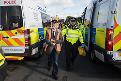 Metropolitan Police officers arrest Insulate Britain climate activists who had previously blocked a M25 slip road at Junction 14 close to Heathrow airport as part of a campaign intended to push the UK government to make significant legislative change to start lowering emissions on 27th September 2021 in Colnbrook, United Kingdom. The activists are demanding that the government immediately promises both to fully fund and ensure the insulation of all social housing in Britain by 2025 and to produce within four months a legally binding national plan to fully fund and ensure the full low-energy and low-carbon whole-house retrofit, with no externalised costs, of all homes in Britain by 2030.