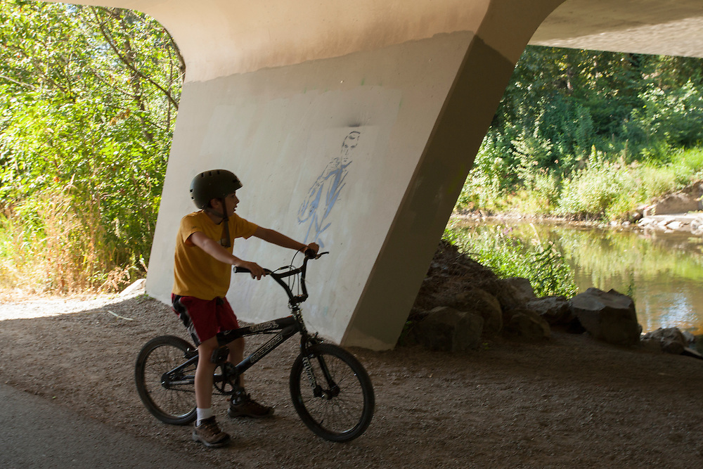 United States, Washington, Redmond, boy on bicycle under bridge on Sammamish River Trail