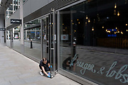 Readying to re-open a burger and lobster restaurant business, a females employee wipes down door surfaces during the Coronavirus pandemic in the City of London, the capitals financial district, on 6th August 2020, in London, England.