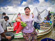 13 JUNE 2013 - YANGON, MYANMAR:   A woman carrying a fish gets off of a cross river boat at the Aung Mingalar Jetty in Yangon. The jetty is a stop for commuters who live on the far side of the Irrawaddy River and ride small boats back and forth across the river. Yangon, formerly Rangoon, is Myanmar's commercial capital and used to be the national capital. The city is on the Irrawaddy River and has a vibrant riverfront.  PHOTO BY JACK KURTZ