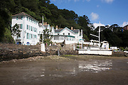 """Portmeirion, in North Wales, is a resort, where no one has ever lived. A self-taught Welsh architect named Sir Clough Williams-Ellis built it out of architectural salvage between the 1920s and 1970s, loosely based on his memories of trips to Portofino. Including a pagoda-shaped Chinoiserie gazebo, some Gothic obelisks, eucalyptus groves, a crenellated castle, a Mediterranean bell tower, a Jacobean town hall, and an Art Deco cylindrical watchtower. He kept improving Portmeirion until his death in 1978, age 94. It faces an estuary where at low tide one can walk across the sands and look out to sea. At high tide, the sea is lapping onto the shores. Every building in the village is either a shop, restaurant, hotel or self-catering accomodation. The village is booked out at high season, with numerous wedding receptions at the weekends. Very popular amongst the English and Welsh holidaymakers. Many who return to the same abode season after season. Hundreds of tourists visit every day, walking around the ornamental gardens, cobblestone paths, and shopping, eating ice-creams, or walking along the woodland and coastal paths, amongst a colourful assortment of hydrangea, rhododendrons, tree ferns and redwoods. The resort boasts two high class hotels, a la carte menus, a swimming pool, a lifesize concrete boat, topiary, pools and wishing wells. The creator describes the resort as """"a home for fallen buildings,"""" and its ragged skyline and playful narrow passageways which were meant to provide """"more fun for more people."""" It does just that.///Portmeirion Hotel overlooking the estuary Afon Dwyryd towards Porthmadog and Tremadog. With the 'Amis Reunis Stone boat'"""