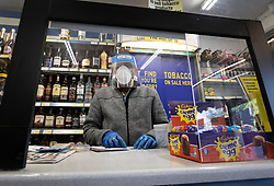 © Licensed to London News Pictures. 19/04/2020. Fetcham, UK. The owner of the Holiday News newsagents shop wears full protective face mask, visor and gloves as he serves from behind a newly installed safety screen in Fetcham, Surrey. The government have announced that lockdown will continue for another three weeks. The public have been told they can only leave their homes when absolutely essential, in an attempt to fight the spread of the coronavirus COVID-19 disease. Photo credit: Peter Macdiarmid/LNP