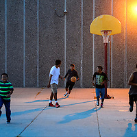 Darnel Dean, center, rushes down court as a group of friends plays a game of basketball Thursday at Tohatchi High School.