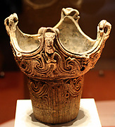 Jomon crown pot. The protrusions on the rim of this crown pot may have been inspired by the architecture of Jomon houses. The crown pot appears rigid in comparison to the fluid form of the flame pot. These contrasting styles seem to be important in Jomon culture and can be seen in the arrangement of buildings and burials.