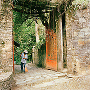 A groundsman sweeps the front gate at the Edward James Surrealist Gardens at Las Pozas, Xilitla, Mexico
