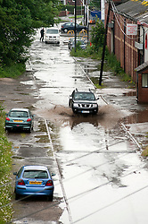 A dark Nissan 4x4 gives some indication of the amount of rainfall as it makes its way along the flooded lane.28 June 2012.Image © Paul David Drabble