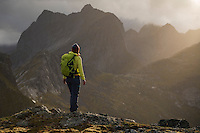 Female hiker on summit of Tverrfjellet with view over distant mountains, Lofoten Islands, Norway