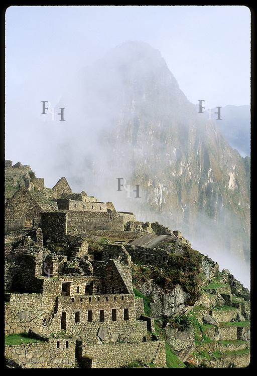 Lowest ruins of city catch sunrise as sacred Huayna Picchu peak emerges from fog;(v)Machu Picchu Peru