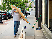 31 MAY 2020 - DES MOINES, IOWA: A worker carries a sheet of plywood into a pizza restaurant and bar that had its windows shattered by rioters in downtown Des Moines very early Sunday morning. A group of rioters, protesting the death of George Floyd in police custody in Minneapolis, smashed windows in businesses and restaurants around the Polk County Courthouse in Des Moines. Des Moines police said they made 25 arrests Saturday night and very early Sunday morning. No one was hurt in the disturbances.     PHOTO BY JACK KURTZ