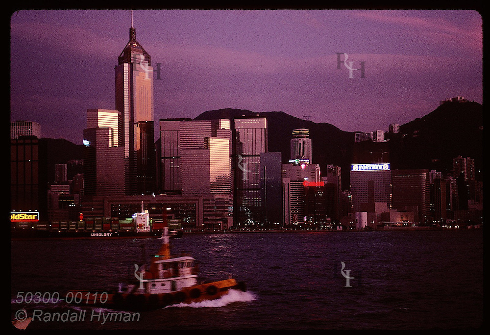 Skycrapers catch last glow of sunset as tugboat motors by; view of Hong Kong from Kowloon side. Hong Kong