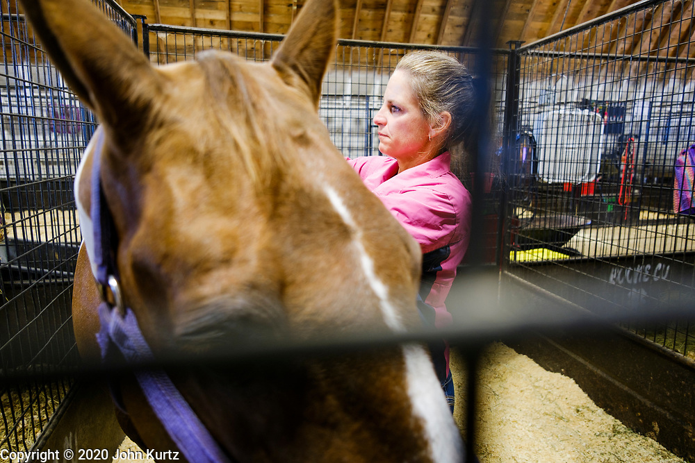 16 JULY 2020 - BOONE, IOWA: A woman grooms her daughter's horse on the first day of the Boone County Fair in Boone. Summer is county fair season in Iowa. Most of Iowa's 99 counties host their county fairs before the Iowa State Fair. In 2020, because of the COVID-19 (Coronavirus) pandemic, many county fairs were cancelled, and most of the other county fairs were scaled back to concentrate on 4H livestock judging. Boone county scaled back its fair this year. The Iowa State Fair was cancelled completely.             PHOTO BY JACK KURTZ
