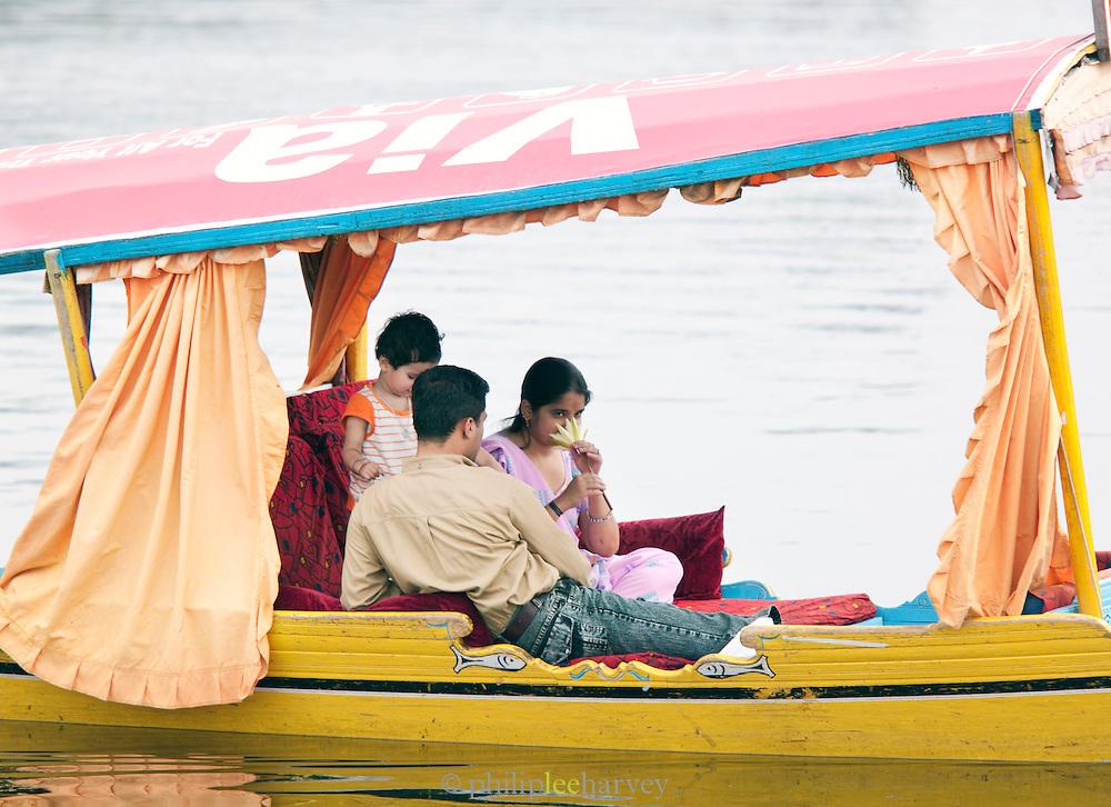 A local family travel by Shikara, a local wooden boat, on Lake Dal, Srinigar, Kashmir, India
