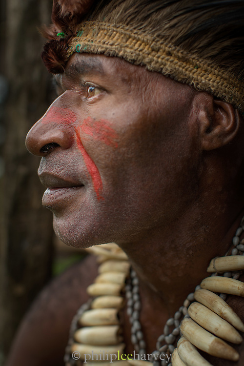 Man in traditional tribal dress, wearing a necklace of crocodile teeth, Miwa Village, Lake Murray, Middle Fly District, Western Province, Papua New Guinea