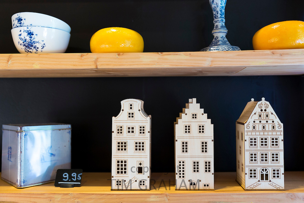 Gouda cheese wheels and traditional Dutch ceramic houses ornaments in cheese shop in Jordaan district, Amsterdam, Holland