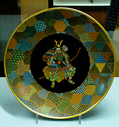 Dish- unsigned, attributed to Seizaburo Goto of Honcho-dori, Yokohama, 1875-80.  The decoration features a seated samurai and, on the reverse, butterflies and flowers.  This mix of styles and motifs reflects western tastes and the increase in mass product