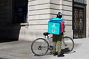 A delivery cyclist for gig economy giant Deliveroo idles beside a cash point with an insulated takeaway box on his back on 15th July, 2021 in Leeds, United Kingdom. British company Deliveroo reported a quarterly increase of food orders nearing 90% as people continue to have food delivered to them despite Covid-19 restrictions easing.
