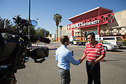 Shopper Armand Dotimas of San Jose is interviewed by media as Milpitas Police investigate a homicide that occurred inside the Sports Authority store at the Great Mall in Milpitas, California, on June 7, 2013.  One man was killed and another quickly taken into custody.  Police say there are no outstanding suspects. (Stan Olszewski/SOSKIphoto)