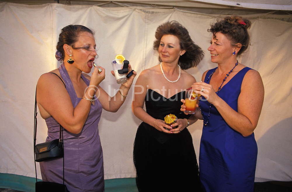 Two friends watch lipstick technique as a lady applies a layer to her lips while holding her cocktail before entering a party held in a marquee at the Royal Navy Air Station Culdrose, on 14th May 1998, at Culdrose, Devon, England.