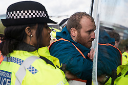 Insulate Britain spokesperson Liam Norton is arrested after  a slip road from the M25 at Junction 14 close to Heathrow is blocked by Insulate Britain as part of a campaign intended to push the UK government to make significant legislative change to start lowering emissions on 27th September 2021 in Colnbrook, United Kingdom. The activists are demanding that the government immediately promises both to fully fund and ensure the insulation of all social housing in Britain by 2025 and to produce within four months a legally binding national plan to fully fund and ensure the full low-energy and low-carbon whole-house retrofit, with no externalised costs, of all homes in Britain by 2030.