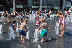 © licensed to London News Pictures. London, UK 25/07/2012. Children enjoying hot weather as they play with fountains outside the City Hall on 25/07/12. Photo credit: Tolga Akmen/LNP
