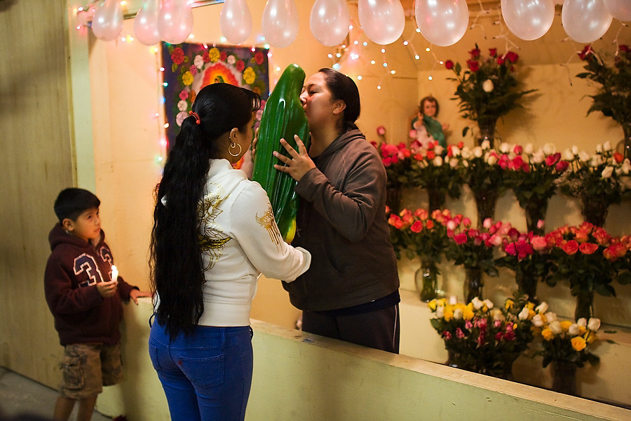 A woman tenderly kisses a statue of the Virgen de Guadalupe during the Fiesta de la Hispanidad, commemorating the coronation of the Virgen de Guadalupe as queen of the hispanic world at Hudson Valley Foie Gras in Ferndale, New York on October 11, 2008. The shrine of balloons and flower in honor of Mexico's patron saint was built inside the factory. Some of the workers and their families, practically all Mexican immigrants, live on the grounds of the factory in company provided housing; a small, isolated Mexican community flourishes in the Catskills.