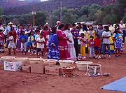 Baskets of food and candy that children will grab following Carla's runs, Carla's mother and aunt beyond, Carla Goseyun's White Mountain Apache Traditional Sunrise Ceremony, Whiteriver, Arizona.  Please Note: A small extra licensing fee needs to be paid to the Goseyun Family for usage of this photo. Contact Fred Hirschmann for more information. Thanks.